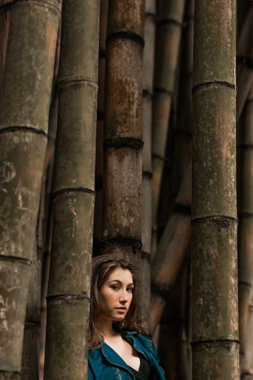 woman standing beside bamboo