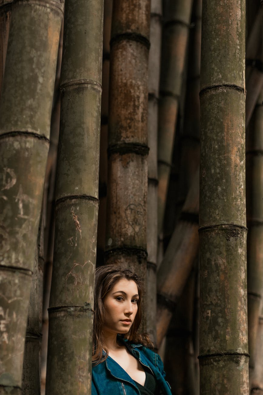 woman standing beside bamboo